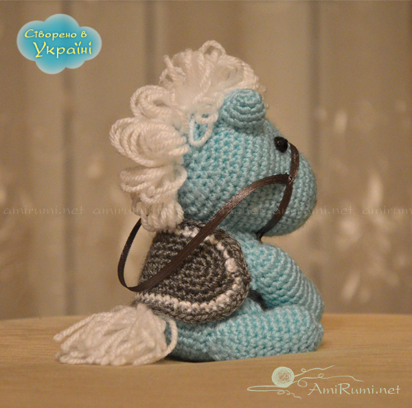 Crocheted amigurumi toy war-horse sitting