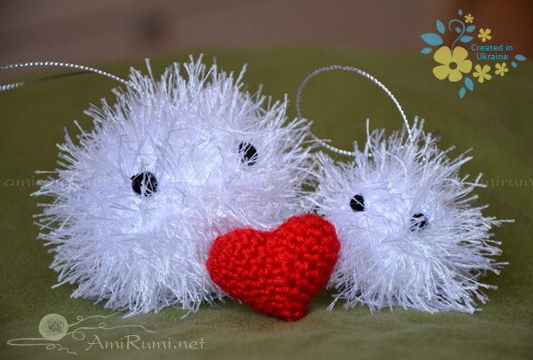 two amigurumi toys snowballs with red heart